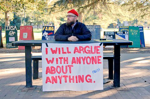 man at table in park with sign; 'I will argue with anyone about anything'